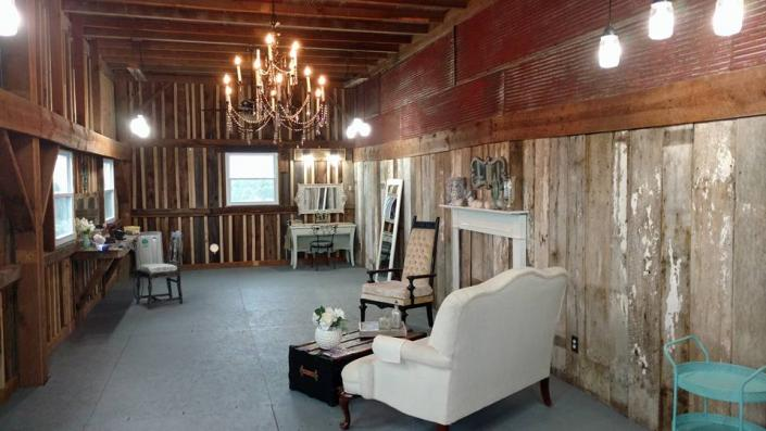 The area is decorated in a rustic fashion with plush seating and makeup stands. A chandelier hangs from the wooden ceilings adding an elegant touch.