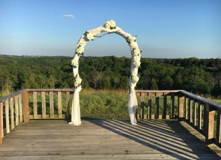 [Image: Outdoor wedding ceremony decorations don't compete with the beauty of nature, they enhance it. This beautiful wedding arch is decorated with white fabric and white flowers. ]