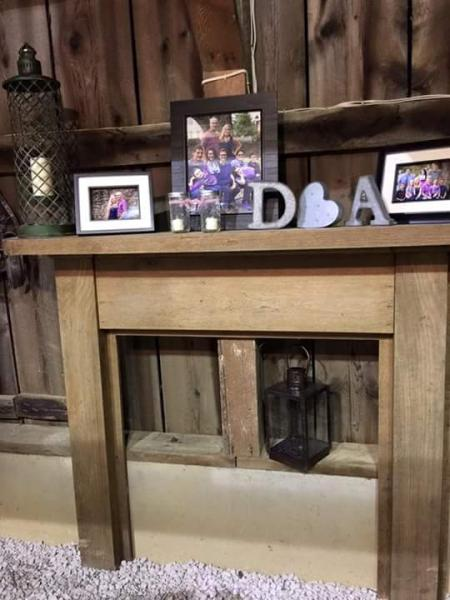 Wooden fireplace mantel with picture frames and other small decorations. This mantel is beautiful and gives a sense of home to your wedding reception. Your guests will definitely feel welcomed!