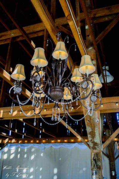[Image: Chandeliers scream wedding! This beautiful vintage piece hanging from the wooden open ceilings adds a touch of elegance to our already beautiful barn venue.]