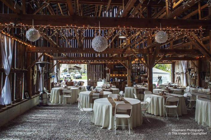 [Image: This beautiful barn with wooden open ceilings adds a rustic touch to your wedding reception. Lights hanging from the ceiling, white tablecloths and simple decor gracefully compliment the vintage venue. ]